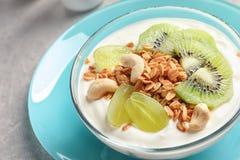 Bowla med yoghurt, frukter och granola på tabellen arkivbilder