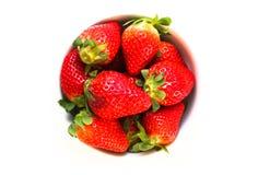 Bowla mycket av nya och naturliga röda jordgubbar med gröna sidor som isoleras på en sömlös vit bakgrund Royaltyfri Foto