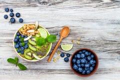 Bowlar smoothies för superfoods för frukost Matcha för grönt te överträffat med chia-, lin- och pumpafrö, bipollen, granola, koko royaltyfria foton
