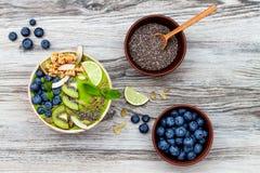 Bowlar smoothies för superfoods för frukost Matcha för grönt te överträffat med chia-, lin- och pumpafrö, bipollen, granola, koko arkivfoto