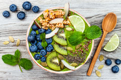 Bowlar smoothies för superfoods för frukost Matcha för grönt te överträffat med chia-, lin- och pumpafrö, bipollen, granola, koko Arkivfoton