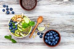Bowlar smoothies för superfoods för frukost Matcha för grönt te överträffat med chia-, lin- och pumpafrö, bipollen, granola, koko royaltyfria bilder