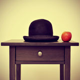 Bowler hat and apple, homage to Rene Magritte painting The Son o. Picture of a bowler hat and an apple on a bureau, homage to Rene Magritte painting The Son of stock photo