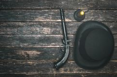 Bowler hat and gun. Musket gun, bowler hat and burning candle on wooden table background. Duel royalty free stock photos