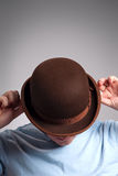 Bowler hat man. Portrait of man covering his face with bowler hat stock images