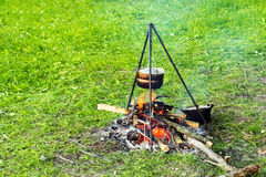 Bowler on a tripod over a fire, cooking food in a field tent camp Stock Photography