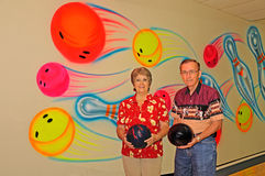 Bowlers. Two bowlers with bowling balls against a colorful wall at the alley Stock Photography