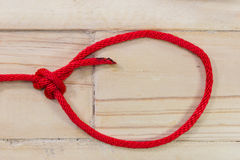Bowline knot made from red synthetic rope, tightening on wooden. Background stock image