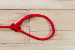 Bowline knot made from red synthetic rope, tightening on wooden. Background stock photography