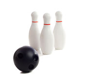 Bowling. A plastic bowling ball rolling towards three pins, isolated against a white background Royalty Free Stock Photos