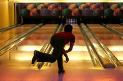 Bowling. Photo of a bowling player who has just rolled the ball, which can't be seen because of the player's silhouette Royalty Free Stock Image