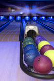 Bowling alley with balls. In blue, psychedelic colors Royalty Free Stock Image