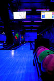 Bowling alley lit by blacklight with neon colors Stock Photo