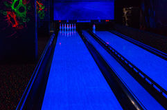 Bowling alley lit by blacklight with neon colors Stock Image