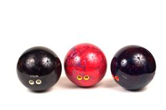 Bowling Arsenal. 3 bowling balls photographed in a group with finger holes and finger grips visible.  One ball has a date stamped above holes Royalty Free Stock Images