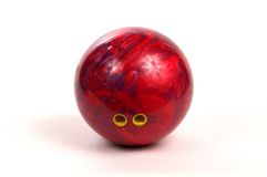 Bowling Ball. Red and Purple bowling ball with finger holes visible,  Finger holse have yellow grips Royalty Free Stock Photos