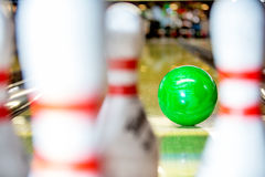 Bowling ball approaching pins. A bowling ball about to hit the pins on a 10 pin bowling alley, seen from the point of view of one of the pins Royalty Free Stock Images