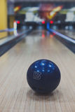 Bowling ball closeup on lane background. Bowling accessories background. Interior of bowling alley, lane with ball closeup, selective focus. Vertical Royalty Free Stock Images