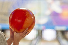 Bowling ball and hand. Female hands holding orange bowling ball Royalty Free Stock Images