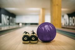 Bowling ball and house shoes on lane closeup view royalty free stock images