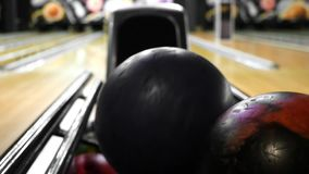 Bowling ball out of ball return. Media. ball was rolled out, vari colored bowling balls lie in bowling club.  stock footage