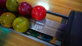 Bowling Ball out of Ball Return.Bowling game. Bowling balls lie on stand close up. Player holds bowling ball with hand stock footage