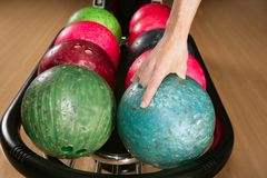 Bowling ball in player man hand. In colorful rows Royalty Free Stock Photo