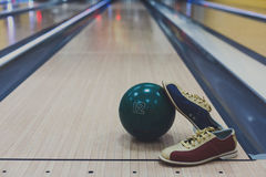 Bowling ball and shoes on lane background. Bowling accessories background with copy space. Interior of bowling alley, lane with ball and special shoes Stock Images