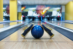 Bowling ball and shoes on lane background. Bowling accessories background. Interior of bowling alley, lane with ball and special shoes Royalty Free Stock Images