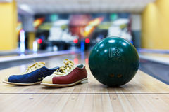Bowling ball and shoes on lane background. Bowling accessories background. Interior of bowling alley, lane with ball and special shoes closeup, selective focus Royalty Free Stock Images