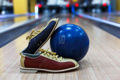 Bowling ball and shoes on lane background. Bowling accessories background. Interior of bowling alley, lane with ball and special shoes closeup, selective focus Stock Images