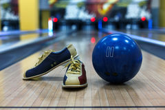 Bowling ball and shoes on lane background Royalty Free Stock Images
