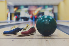 Bowling ball and shoes on lane background. Bowling accessories background. Interior of bowling alley, lane with ball and special shoes closeup, selective focus Royalty Free Stock Photo