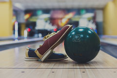 Bowling ball and shoes on lane background. Bowling accessories background. Interior of bowling alley, lane with ball and special shoes closeup, selective focus Royalty Free Stock Photos