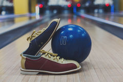 Bowling ball and shoes on lane background. Bowling accessories background. Interior of bowling alley, lane with ball and special shoes closeup, selective focus Stock Photos