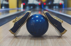 Bowling ball and shoes on lane background. Bowling accessories background. Interior of bowling alley, lane with ball and special shoes closeup, selective focus Royalty Free Stock Photography