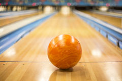 Bowling ball sitting in a colorful bowling alley lane Royalty Free Stock Photo