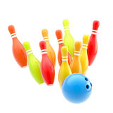 Bowling ball smashing to colorful pins isolated. Bowling blue glossy ball smashing to colorful pins isolated on white Royalty Free Stock Photo