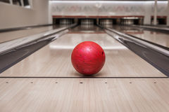 Red bowling ball on the track in the bowling center Royalty Free Stock Photography