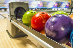 Bowling balls. Colored Bowling balls in a return rack royalty free stock photos