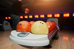 Bowling balls at bowl lift with ultraviolet lighting background. Player Stock Images