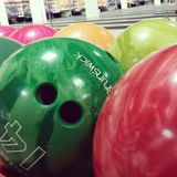 Bowling balls - Brunswick. Bowling balls, yellow, pink, green, red. Rack for bowling balls with interior on background Royalty Free Stock Photos