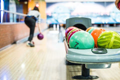 Bowling Balls. Colorful bowling bows with a woman player in the background stock photos