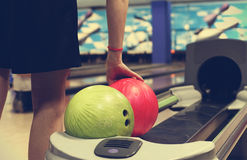 Bowling balls. Girl takes a Ball from the stand for bowling balls Stock Photo