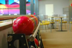 Bowling balls on a rack. A picture of a rack of colorful bowling balls in a bowling alley with some chairs and tables in the background Royalty Free Stock Photos