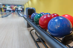 Bowling balls return machine, alley background. Bowling background. Interior of bowling alley lane with balls return machine closeup, selective focus on blue Stock Photography