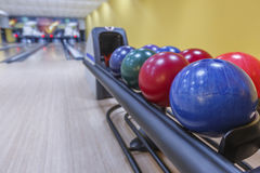 Bowling balls return machine, alley background. Bowling background. Interior of bowling alley lane with balls return machine closeup, selective focus on blue Royalty Free Stock Photo