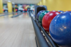 Bowling balls return machine, alley background. Bowling background. Interior of bowling alley lane with balls return machine closeup, selective focus on blue Royalty Free Stock Photos
