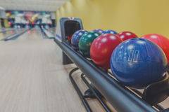 Bowling balls return machine, alley background. Bowling background. Interior of bowling alley lane with balls return machine closeup, selective focus on blue Stock Photos