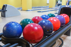 Bowling balls return machine, alley background. Bowling background. Interior of bowling alley lane with balls return machine closeup, selective focus on blue Stock Images
